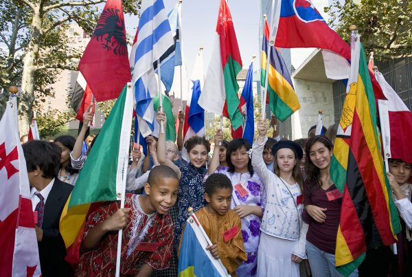 At the United Nations Children represent their nations in costume and with flags